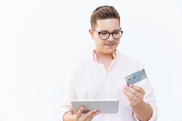 Cliente enfocado usando tableta y tarjeta de crédito