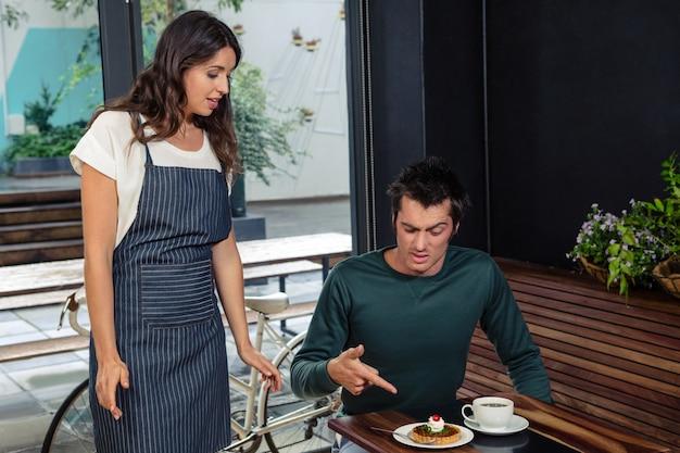 Cliente enojado discutiendo con camarera por orden incorrecta