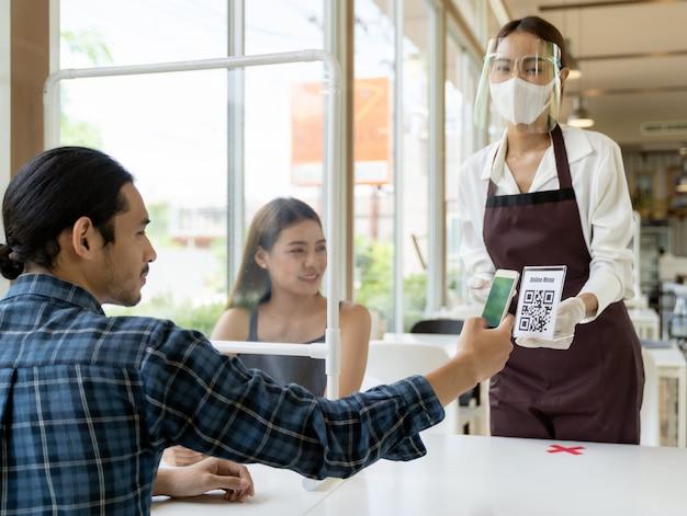 El cliente escanea el menú en línea de la camarera.