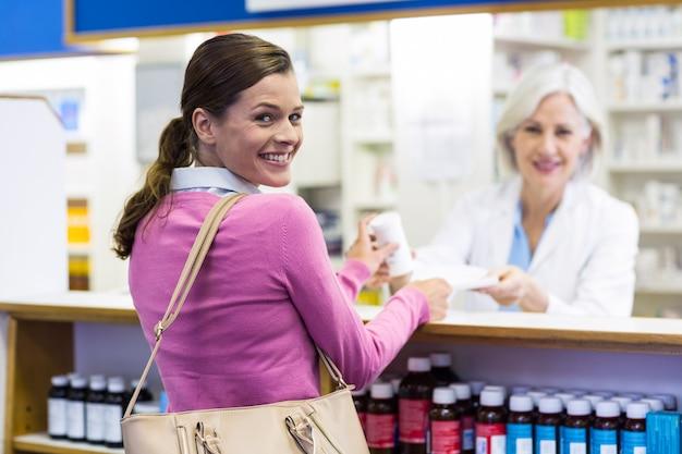 Cliente y farmacéutico sonrientes que sostienen la medicina en farmacia