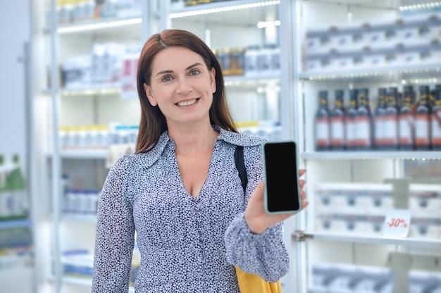 Cliente de farmacia mujer feliz con su smartphone mirando hacia el futuro