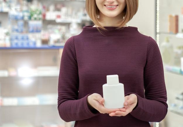 Cliente de la farmacia que sostiene la botella blanca de los cosméticos.