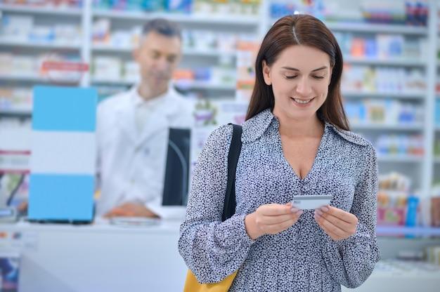 Cliente de farmacia satisfecho mirando una tarjeta de crédito en sus manos
