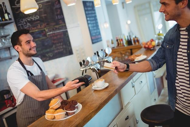 Cliente feliz y camarero en la cafetería.
