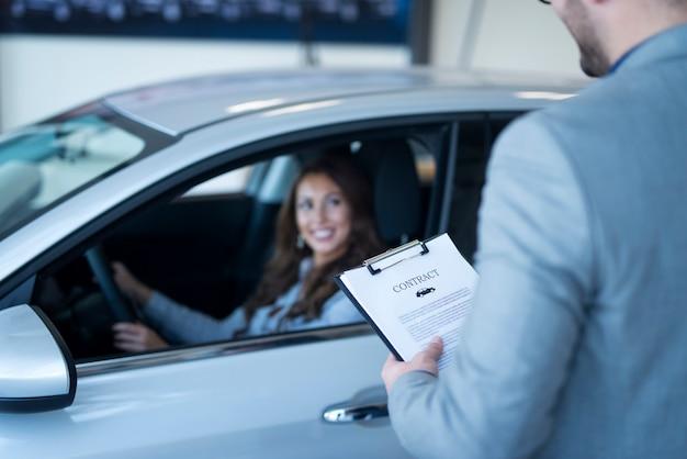 Cliente feliz comprando un coche nuevo en el concesionario de vehículos