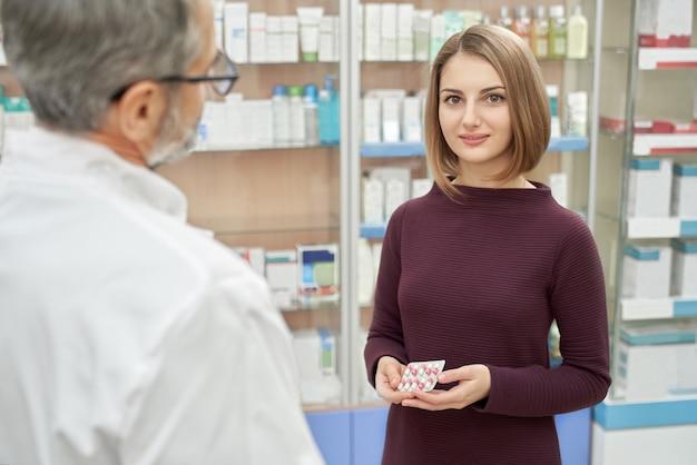 Cliente feliz que presenta en farmacia cerca del farmacéutico.