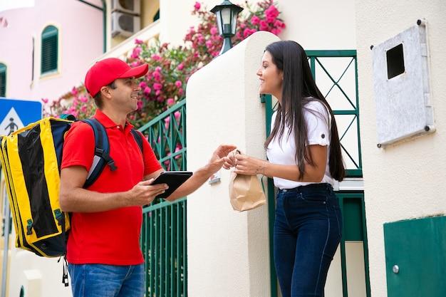 Cliente feliz que recibe el pedido en el paquete del servicio de mensajería. repartidor caucásico en uniforme rojo con bolsa térmica, hablando con el cliente y entregando el pedido. servicio de entrega y concepto de correo.