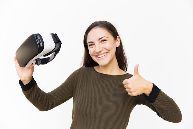 Cliente feliz sonriente que sostiene los auriculares de vr