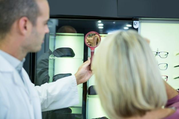 Cliente femenino con gafas y check-in espejo