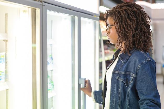 Cliente femenino negro joven que estudia los estantes del refrigerador