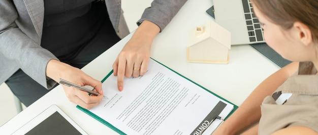 Cliente firma documento para comprar casa y bienes raíces