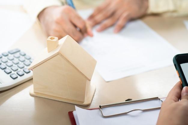 El cliente firma un documento de préstamo hipotecario para comprar viviendas con un agente inmobiliario o un abogado