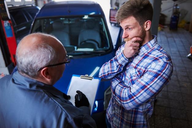 Cliente hablando con un mecánico en el taller.