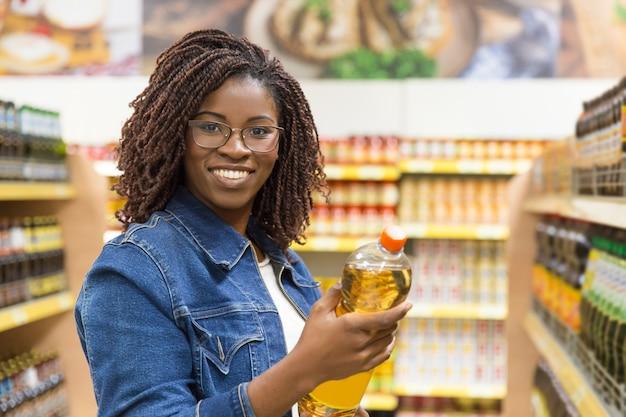 Cliente joven sonriente que sostiene la botella de aceite