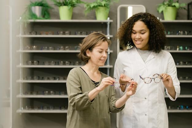 Cliente joven de la tienda de óptica sosteniendo anteojos mientras escucha los consejos de un consultor de raza mixta en bata blanca