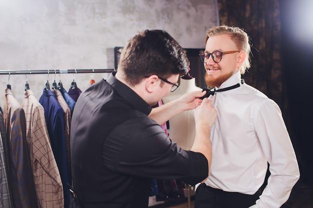 Cliente masculino en el centro comercial probando ropa de negocios ayudado por dependienta