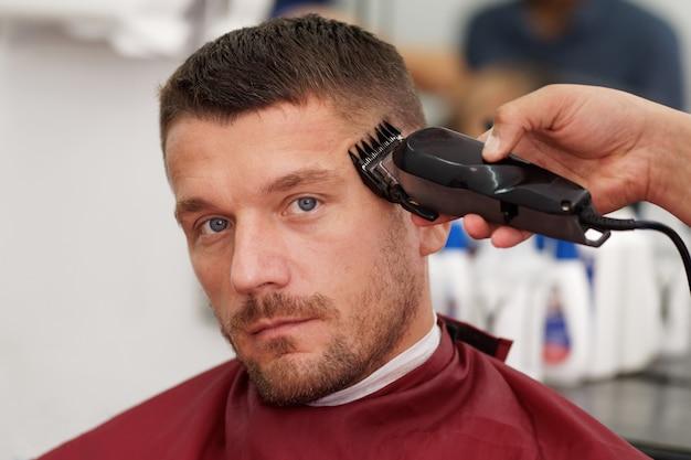 Cliente masculino corte de pelo por peluquero.