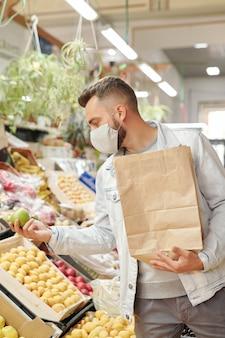 Cliente masculino joven en máscara de tela de pie en el mostrador de alimentos y sosteniendo una bolsa de papel mientras compra manzanas en el mercado de agricultores