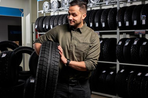 El cliente masculino está satisfecho con la compra de un neumático en el garaje de reparación de automóviles, soporte que sostiene el caucho para el automóvil en las manos, en la tienda de la tienda de automóviles