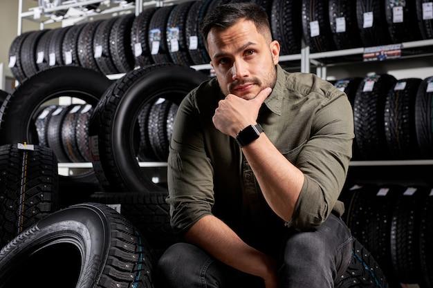El cliente masculino se sienta pensando cuál de los neumáticos comprar, un chico caucásico con ropa casual se sienta en contemplación en el taller de servicio de automóviles, rodeado de neumáticos negros para el automóvil
