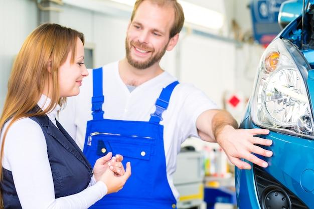 Cliente y mecánico de automóviles en taller.