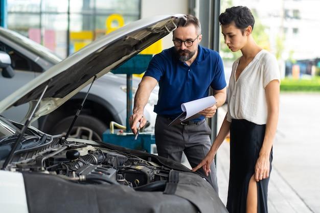 Cliente mecánico hombre y mujer comprobar el estado del coche antes de la entrega. garaje de la estación de mantenimiento de reparación de automóviles.