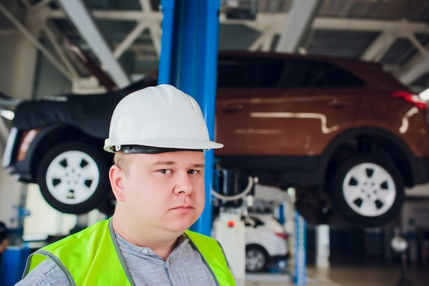 El cliente mira el trabajo en una rueda de taller de automóviles debajo del automóvil en servicio