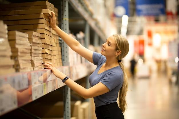 Cliente mujer alegre mirando hacia arriba y tirando del producto en el estante mientras compra en la ferretería