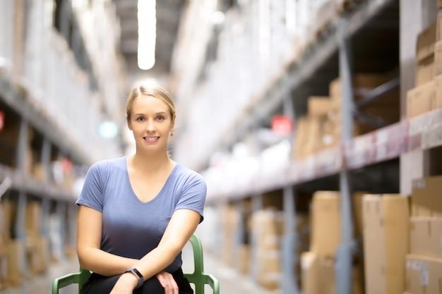 Cliente mujer alegre mirando a cámara y sentado en la silla mientras compras en ferretería