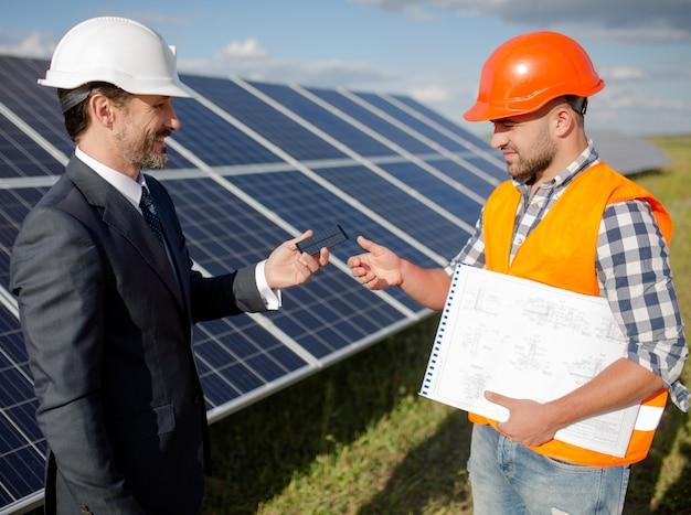 Cliente de negocios extendiendo el artículo fotovoltaico a capataz.