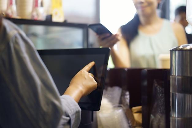El cliente pide comida y bebida con el uso de su teléfono inteligente y de la alta tecnología de nfs para pagarle a un barista