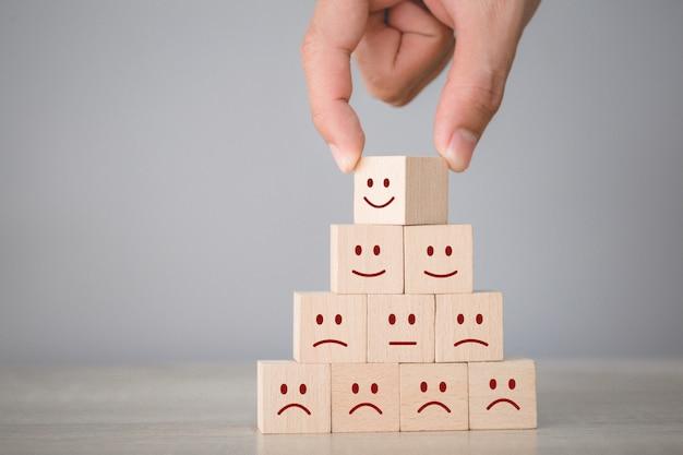 Cliente presionando emoticon de cara sonriente en cubo de madera, calificación de servicio, concepto de satisfacción.