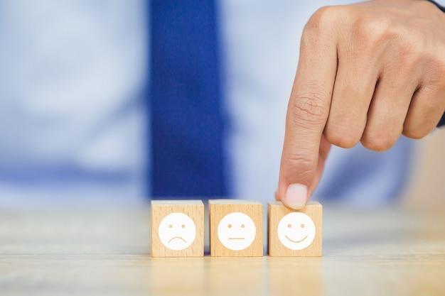 Cliente presionando emoticon de cara sonriente en cubo de madera