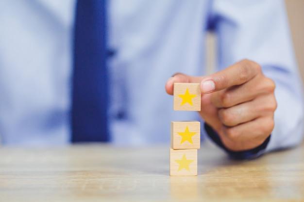 Cliente presionando estrella en cubo de madera, calificación de servicio, concepto de satisfacción.