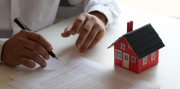Cliente que firma un contrato sobre el contrato de préstamo para una nueva casa