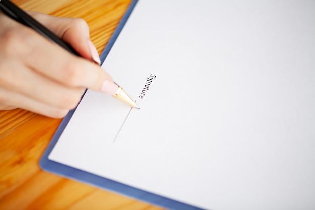 Cliente que firma el contrato, los términos acordados y la solicitud aprobada y analiza la valoración del préstamo hipotecario, la reunión con el trabajador bancario o el agente inmobiliario