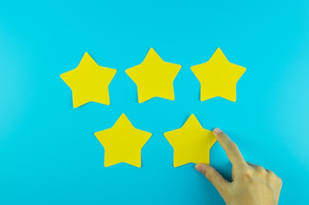 Cliente que lleva a cabo la nota de papel amarilla de cinco estrellas sobre fondo azul. comentarios de los clientes, comentarios, calificación, clasificación y concepto de servicio.