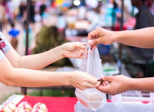 Cliente que paga la factura en efectivo en el mercado al aire libre