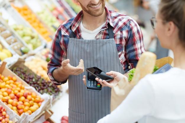 Cliente que paga por teléfono inteligente en el supermercado