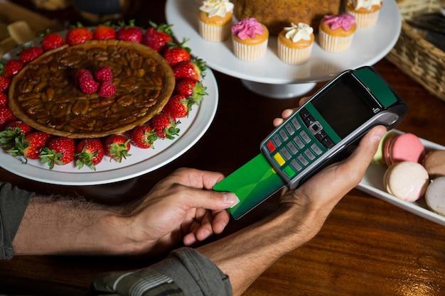 El cliente realiza el pago con tarjeta de crédito en el mostrador.