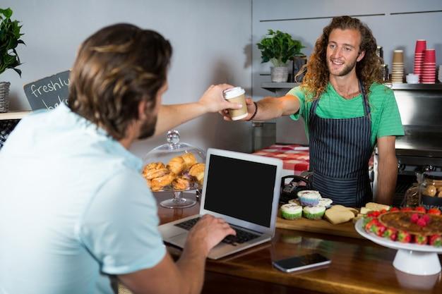 Cliente recibiendo un café del personal del mostrador