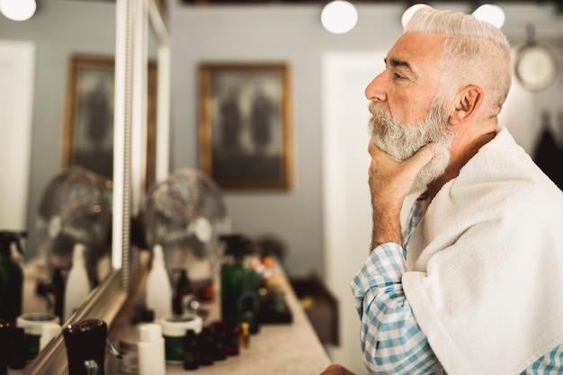 Cliente senior estimando trabajos de barbero en espejo.