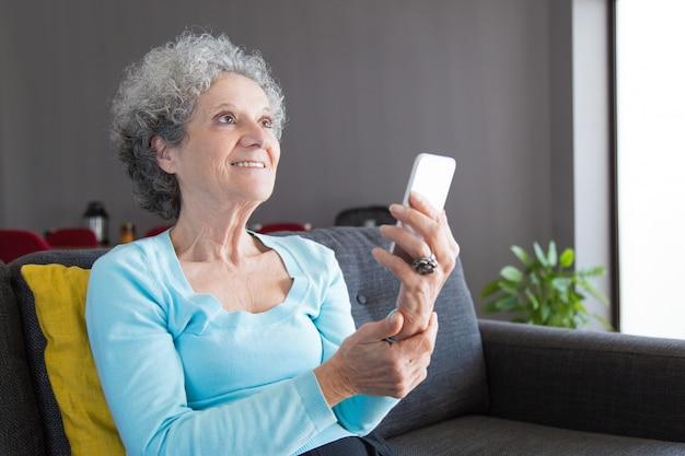 Cliente senior feliz usando teléfono inteligente