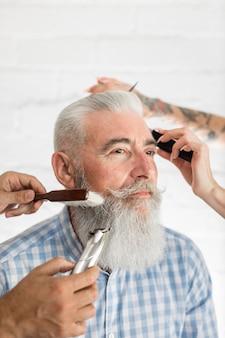 Cliente senior recibiendo barba y cuidado del cabello.
