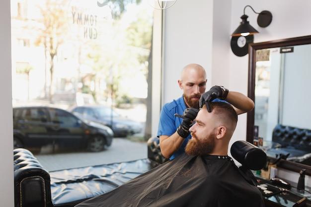 Cliente de servicio de peluquería profesional masculino, afeitado de barba grande y gruesa con navaja de afeitar