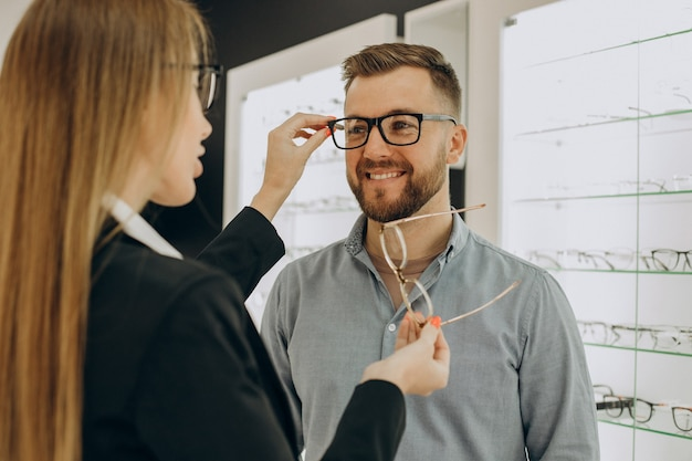 Cliente shoosing anteojos en tienda óptica con la ayuda del vendedor