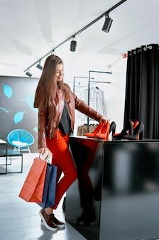 Cliente sonriente que elige los zapatos del tacón alto en la tienda moderna.