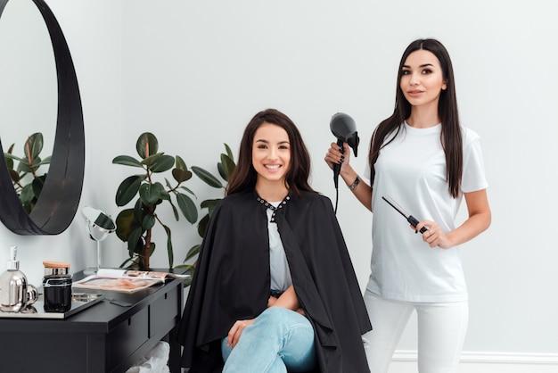 El cliente sonriente se sienta en la silla del peluquero, el peluquero está de pie junto a ella con el secador y el peine en sus manos.