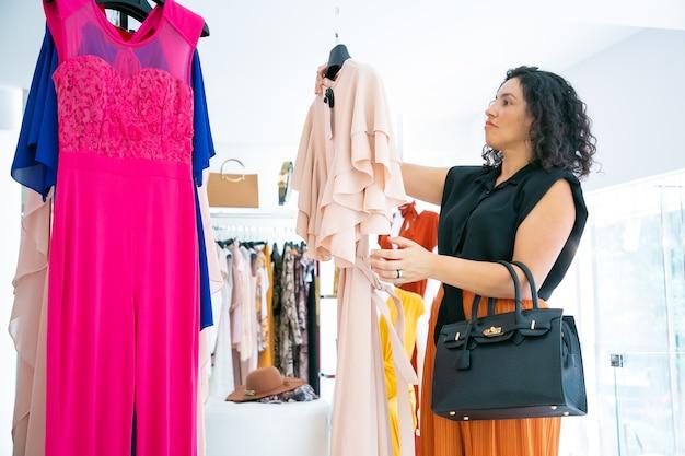 Cliente de la tienda de moda pensativa que toma el vestido con la etiqueta del estante para probar. plano medio, vista lateral. consumismo o concepto minorista