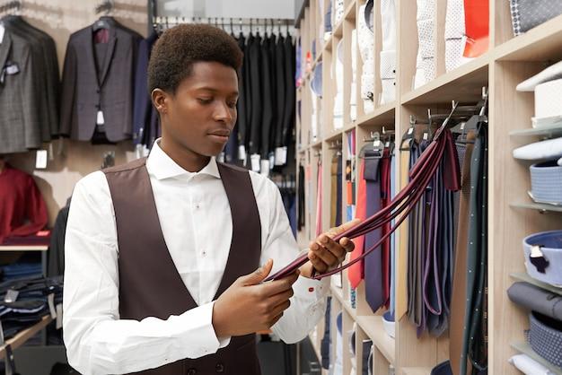 Cliente de la tienda que elige la corbata en una elegante boutique.